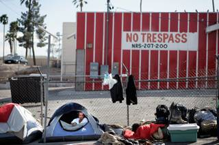 A homeless man camps with others inside tents along Foremaster Lane between Las Vegas Boulevard North and Main Street in Las Vegas on Thursday, April 2, 2009.