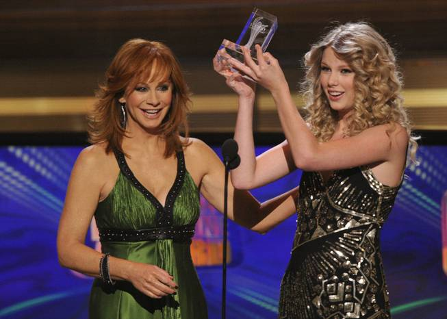 Reba McEntire, left, presents Taylor Swift with the Crystal Milestone award at the 44th Annual Academy of Country Music Awards in Las Vegas on Sunday, April 5, 2009.