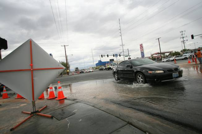 A car drives through water on East Sahara Avenue near the site of a water main break.