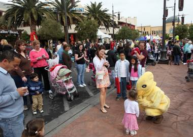 Visitors to Town Square greet the Easter chick on Saturday morning. Town Square had games, booths and more than 35,000 eggs to be collected.