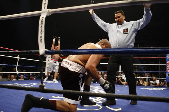 Chris Arreola (left) celebrates as referee Tony Weeks counts out Jameel McCline after he was knocked out in the fourth round of their heavyweight title fight at the Mandalay Bay Events Center in Las Vegas, Nevada, April 11, 2009.
