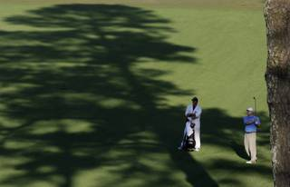 Chad Campbell watches his drive with his caddie Judd Burkett on the 15th fairway during the third round of the Masters golf tournament at the Augusta National Golf Club in Augusta, Ga., Saturday.