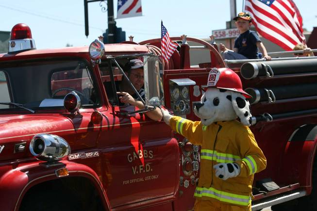 Captain Sparky walks along a fire truck in the Heritage Parade.