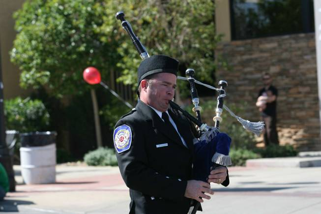 A member of the Henderson Fire Department Honor Guard blows the bag pipes during Henderson's annual Heritage Parade on Water Street.