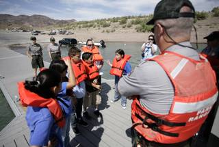 Fifth-grade students from Sandy Searles Miller Elementary School receive instruction on Thursday from Ranger Dave Horne during their participation in Lake Mead National Recreation Area's C.R.E.W. program (Citizens Removing and Eliminating Waste).