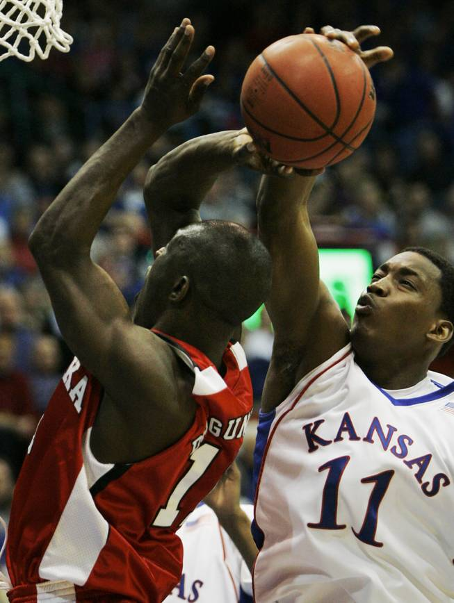 Kansas forward Quintrell Thomas, right, blocks a shot by Nebraska guard Ade Dagunduro (11) during the second half of their game in Lawrence, Kan., on Feb. 21, 2009. Kansas defeated Nebraska 70-53.