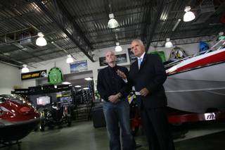 Gov. Jim Gibbons, right, and Dan Boyle, owner of ProShop Motorsports and Marine, discuss the impact of higher taxes on small businesses during a press conference at Boyle's Henderson showroom on Friday.