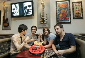 In this photo provided by Hard Rock International, members of the band Panic At The Disco, from left, Ryan Ross, Brendon Urie, Spencer Smith and Jon Walker look over the donated Hard Rock's 2008 Ambassadors of Rock guitar at the Hard Rock Cafe, Thursday, Oct. 9, 2008, in Las Vegas.