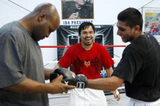 Junior welterweight boxer Manny Pacquiao, center, of Philippines laughs with lightweight boxer Amir Khan, right, of England during a workout in a gym in Las Vegas, Nevada April 30, 2009. Assistant trainer Michael Moorer is at left. Pacquiao will take on Ricky Hatton of England in a 12-round bout at the MGM Grand Garden Arena Saturday.