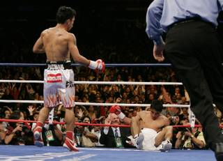 Manny Pacquiao (left), of Philippines, sends Erik Morales, of Mexico, to the mat for the third time during their super featherweight fight at the Thomas & Mack Center in Las Vegas, Nevada on November 18, 2006.