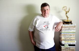 John Hill stands next to his life's work, about 70 scripts and novels written over the past 38 years, inside his Las Vegas home Wednesday, May 6, 2009. Hill won the Emmy in 1991 for his work on