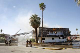 Firefighters work to control a blaze in an apartment building at the old Moulin Rouge hotel and casino on Bonanza Road. The apartments were supposed to have been vacant were destined to be torn down, officials said.