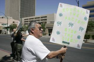 Roque Perea, a medical marijuana patient, joins about a dozen others for the Million Marijuana March on Saturday in front of the Regional Justice Center.
