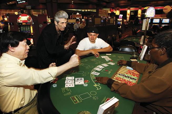 George Boutsifakos, center, co-creator of Two Cards High, advises dealer Phyllis Carter as Stanleu Ko, left, and Jesse Delgado play the game during its test run in April at Boulder Station.