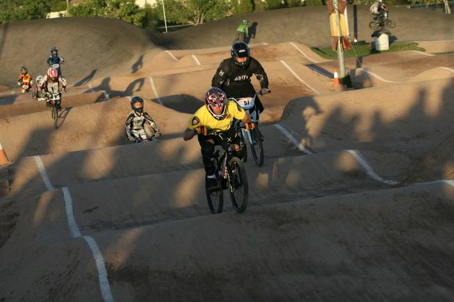 Metro Officer, Michael Kaczmerk, foreground, rides with Boulder City youth during the annual BMX Is Not A Crime event Friday night.