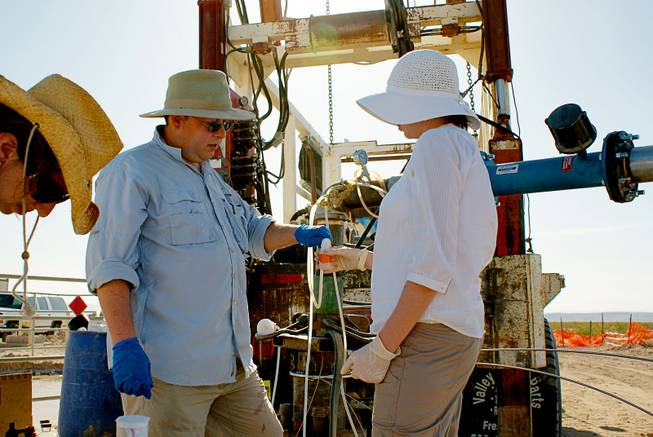 Duane Moser, left, a microbial and molecular ecologist at the Desert Research Institute, and technician Patty Edmiston take underground water samples in the Amargosa Valley in 2010. The sampling was done in collaboration with Nye County Nuclear Waste Repository Project. Moser is part of a team of researchers that just received a $6.6 million NASA grant to explore life underground.