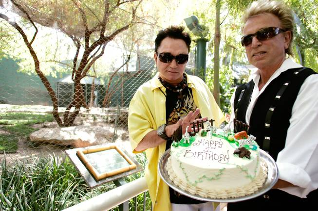 Siegfried Fischbacher, right, and Roy Horn present a birthday cake for their tiger cubs at Siegfried & Roy's Secret Garden at The Mirage.