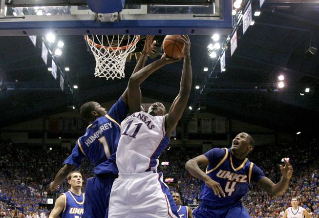 Kansas' Quintrell Thomas (11) gets past UMKC's James Humphrey (1) and Latreze Mushatt (4) to put up a shot during the first half on Nov. 16, 2008, in Lawrence, Kan. Thomas announced his intent to transfer to UNLV on May 22, 2009.