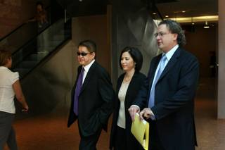 Terrance K. Watanabe, 52, left, of Omaha, Neb., leaves the Regional Justice Center following his arraignment in Las Vegas on Wednesday, accompanied by sister Pam Watanabe-Gerdes and attorney David Chesnoff.