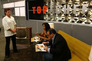 "Robin serves Padma Lakshmi and guest judge Paul Bartolotta a TV dinner during the Quickfire challenge on ""Top Chef: Las Vegas""."
