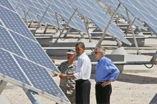 President Barack Obama, accompanied by Senate Majority Leader Harry Reid and Col. Howard Belote, looks at solar panels at Nellis Air Force Base in Nevada on Wednesday.