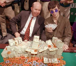 Stu Ungar, a 43-year-old professional gambler from Las Vegas, right, holds up his winning hand during the championship finals in the World Series of Poker, Thursday, May 15, 1997, in Las Vegas. Jack Binion, co-president and part owner of Binion's Horseshoe & Casino where the tournament was being held, watches Ungar after presenting him with his $1 million winnings.