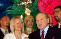 Owner and operator of the Venetian on the Las Vegas Strip, Sheldon Adelson, next to his wife Miriam, left, in front of Las Vegas show girls during the opening of the Las Vegas Sands casino in Macau Tuesday, May 18, 2004.