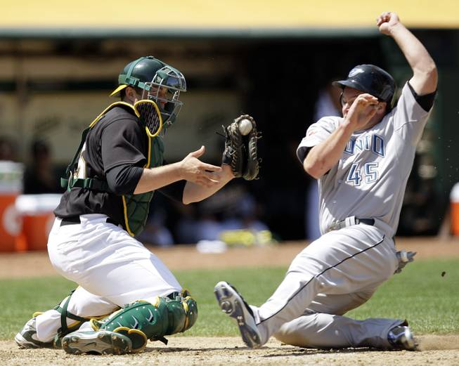 Oakland Athletics catcher Landon Powell, left, waits to tag out Toronto Blue Jays' Travis Snider in the sixth inning of a baseball game Saturday, May 9, 2009, in Oakland, Calif.