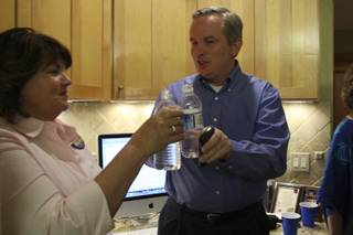 Candidate Cam Walker toasts his water bottle with campaign official Sylvia Harber, left, after the first precinct results showed Walker leading in the race for a seat on the Boulder City Council during his watch party Tuesday at Kirk and Vivian Harrison's home.