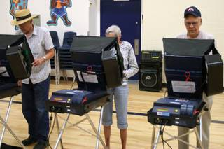 David Sweningsen joins his parents, Jean and Charles, in voting at Garrett Middle School in Boulder City.