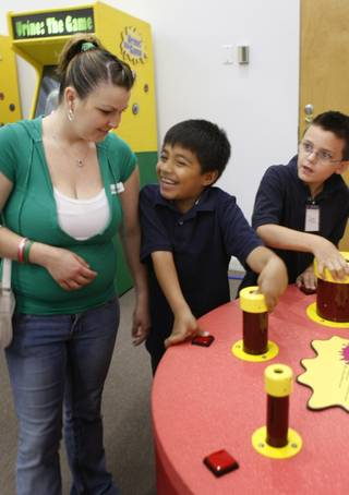Abraham Munoz, center, 8, and his friend Ryan Simpson make farting noises at a display in