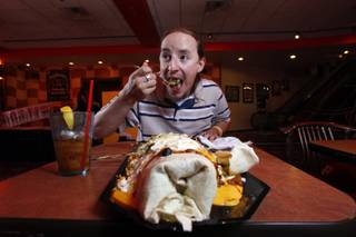 Steven Miller, 25, of Houston, TX, attempts to conquer the B3 Burrito, a massive six-pound, 24 inch burrito, at the NASCAR Cafe in the Sahara Friday, June 19, 2009. Many have tried to eat it, few have succeeded.