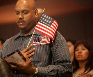 Venkatesh Sunder Tittle, originally from India, recites the Pledge of Allegiance during a Thursday swearing-in ceremony at Las Vegas City Hall. Tittle was one of more than 100 Las Vegas-area residents who participated in the ceremony for new citizens conducted by U.S. Citizen and Immigration Services and the city of Las Vegas.