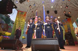 Capt. Raphael Ashe sings the national anthem as the Nellis Air Force Base honor guard, left to right, Sharif Omar, Omar Foster, Travis Skretta and Ulla Stromberg, bring out the colors to start festivities at the Fremont Street Experience.