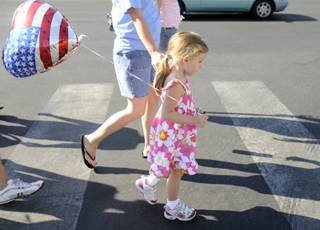 Jordan Ramirez, 4, walks with her mother, Lunde, toward the route of the Summerlin Council Patriotic Parade on Saturday, July 4.