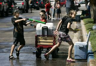 From left, Harley Devorski, Las Vegas, Hunter Brady, Omaha, Neb., and Cezanne Devorski, Las Vegas, chase each other with squirt guns during Damboree festivities in Boulder City on Saturday, July 4.
