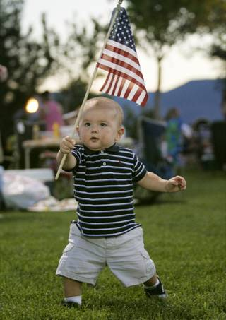 Sebastian Zavila marches around Veterans Memorial Park in Boulder City with an American flag before the start of fireworks Saturday, July 4, 2009.