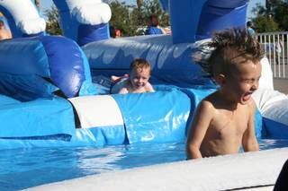 Alex Lee, 6, emerges from the water after a trip down the inflatable slip-and-slide at the Henderson Fourth of July festivities.