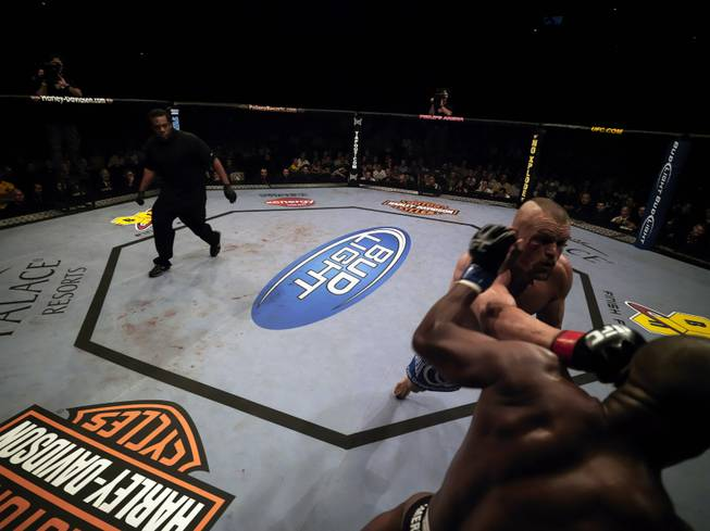 "UFC referee Herb Dean takes a look at the action between Chuck Liddell and Rashad Evans at UFC 88 last September in Atlanta. Evans won the fight with a brutal knockout of ""The Iceman."""