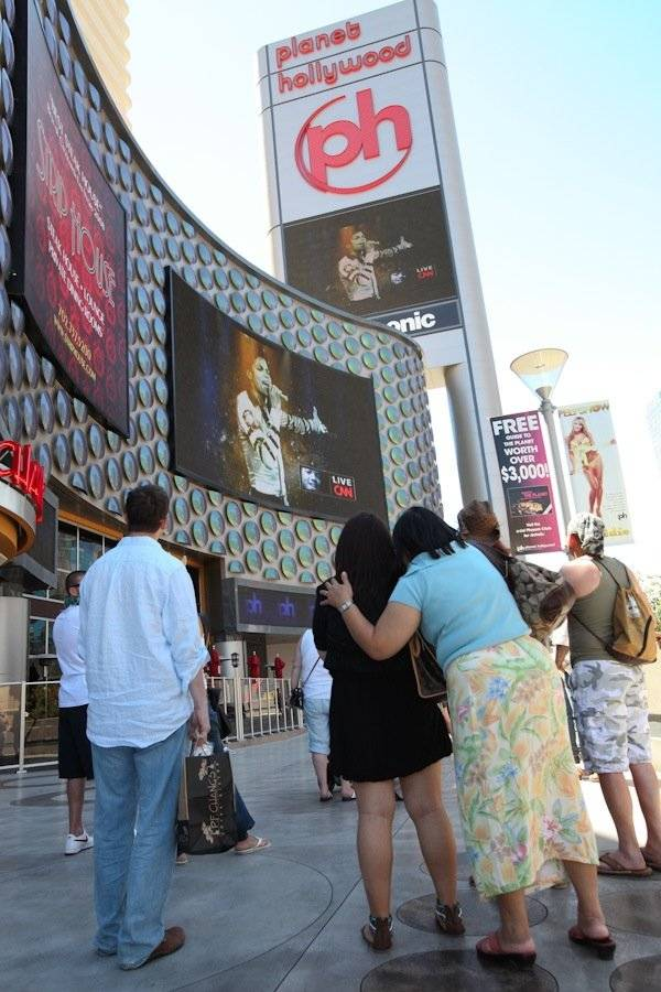 Fans watch the televised Michael Jackson memorial tribute on the video screens at Planet Hollywood.