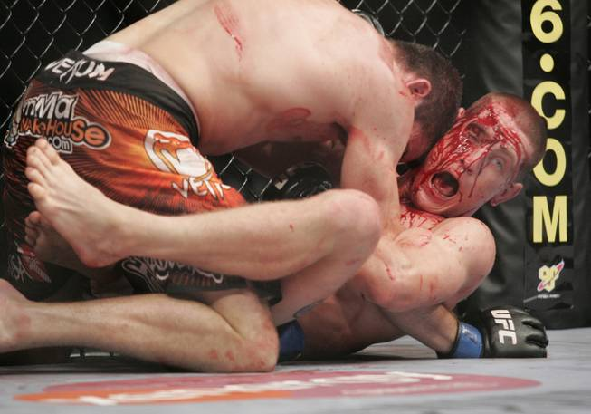 A bloodied Mac Danzig tries to escape Jim Miller during their fight at UFC 100 Saturday, July 11, 2009. Miller won by decision.