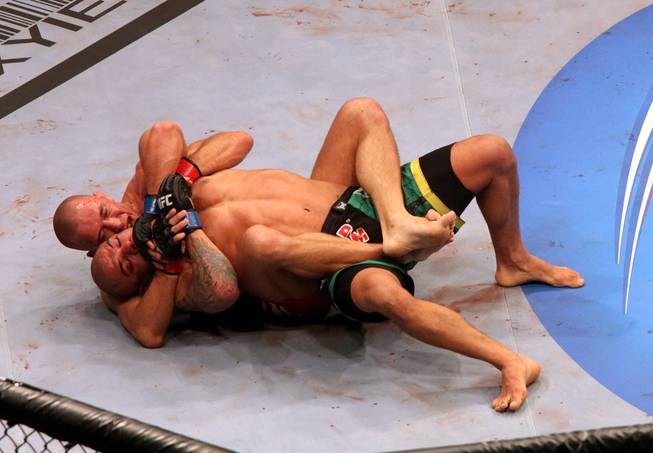 Georges St. Pierre, top, controls Thiago Alves during their UFC 100 match at Mandalay Bay. The welterweight champ retained his title with a unanimous decision victory.