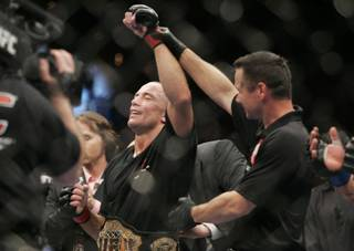 Georges St. Pierre has his arm raised after defeating Thiago Alves in their welterweight title fight at UFC 100. St. Pierre won by decision to retain his title.