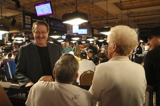 ESPN announcer Norman Chad laughs with fans standing around the tables Tuesday during the 7th day of competition at the World Series of Poker Main Event at the Rio.