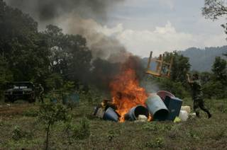 Mexican army soldiers burn laboratory equipment used to produce large quantities of synthetic drugs at a clandestine drug laboratory allegedly run by Mexico's powerful La Familia drug cartel, near the town of Charo, in the state of Michoacan, Mexico, Sunday, July 26, 2009. According to federal law enforcement authorities, the lab produced about 220 pounds (100 kilograms) of methamphetamine or crystal meth,  each week. So far this year, police say they have seized 40 drug labs operated by the La Familia cartel.