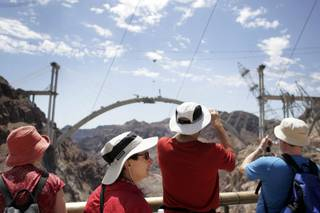 Tourists take in the view of the Hoover Dam bypass bridge from the Hoover Dam observation deck.