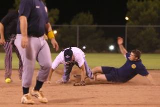 Fire department explorer Jordan Vivone slides in safe at second base under Officer Dave Carpenter Tuesday during the annual National Night Out Boulder City Police-Firefighters' softball game at Veterans Memorial Park.  The police beat the firefighters 14-13.