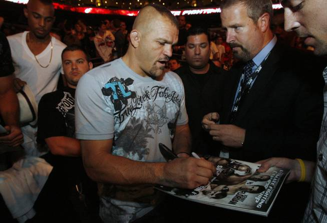 Fans of mixed martial arts and the UFC, Ultimate Fighting Championship gather at the Wachovia Center on Saturday evening August 8, 2009 for a night of fighting. Pictured is fighter Chuck Liddell signing autographs for fans as he enters the seating area before the start of the fights.