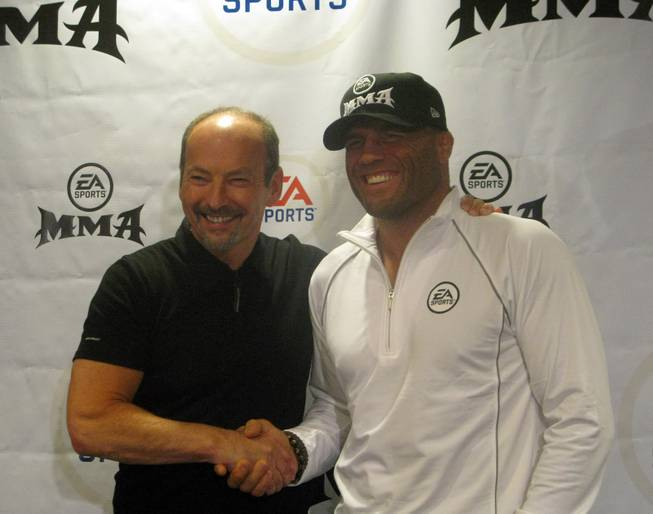 "UFC legend Randy Couture, right, shakes hands with EA Sports president Peter Moore after the announcement Saturday that Couture will appear in company's upcoming ""MMA"" video game."
