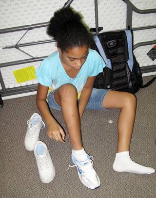 Olivia Rotta tries on a new shoe brought to her by a Zappos employee.